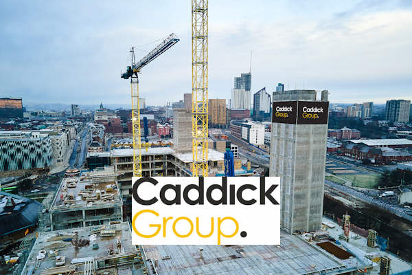 Construction site with completed lift shaft and two tower cranes