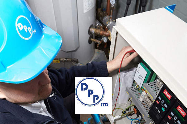 Photo of man wearing blue DPP branded hard hat working on the electrics of a boiler.